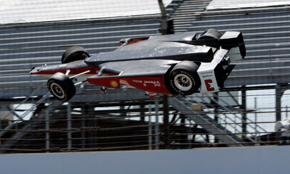 The car driven by Helio Castroneves, of Brazil, is airborne after hitting the wall in the first turn during practice for the Indianapolis 500 auto race at Indianapolis Motor Speedway in Indianapolis, Wednesday, May 13, 2015.  (AP Photo/Joe Watts) ORG XMIT: NAA107