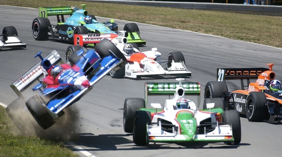 ** AUTO RACING PACKAGE FOR JULY 25 OR THEREAFTER ** Marco Andretti's car goes flying on the first lap after making contact with his teammate Tony Kanaan (11) on Sunday, July 22, 2007 during the IRL Honda 200 auto race at the Mid-Ohio Sports Car Course in Lexington, Ohio. Week in and week out, the races are close, exciting and unpredictable. Yet the IndyCar Series can't seem to escape another kind of series,  a string of off-the-track flare-ups and on-the-track controversies. (AP Photo/Mansfield News Journal, Jason J. Molyet) ORG XMIT: OHMAN501